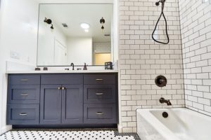 Black and white themed bathroom with subway tile, large mirror and mosaic flooring.
