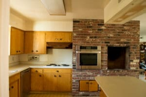 Old wood cabinets with formica counters. Brick wall with built in appliance.