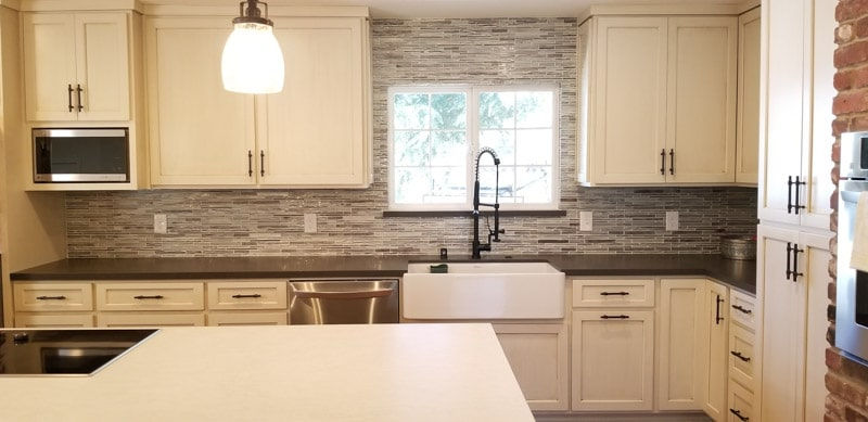 new remodeled kitchen with quartz counters and glass tile