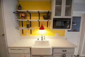 Gray cabinet kitchen remodel with shelves, barn sink and red sink light