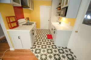 50's Style kitchen remodel with busy tile flooring and glass upper cabinets
