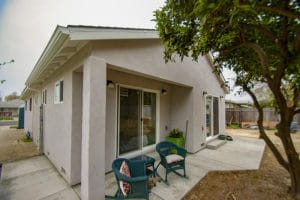 Addition with freshly painted stucco, concrete porch and double sliding doors.