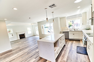Renovation with white waterfall quartz island, white cabinets and view into the living room with tray ceiling.