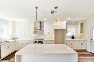 White kitchen remodel with waterfall island, lantern tile and black grout.